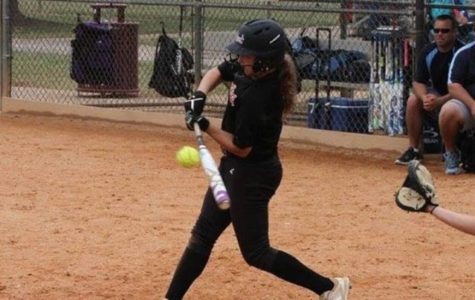Kasidi Staley hits the ball while at bat in a softball game.