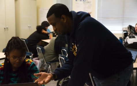 Vince Moore works with and instructs one of his students in class.