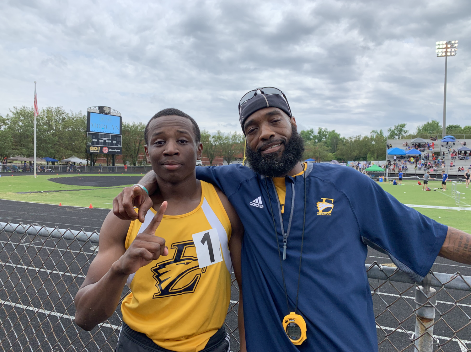 Senior athlete Kyle Goodman poses with Coach Hunter after 800M win.